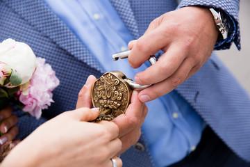 Weddind lock in hands of newlyweds