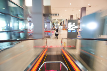 Blur image of people walking down the escalator at airport.