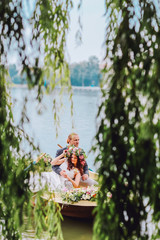 bride and groom sitting in an orange row boat floating out of the tree covering and in to the lake. Bride with wreath of flowers