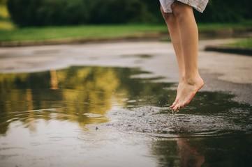 Woman walking barefoot through puddle outdoors