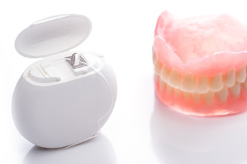 Teeth model with dental floss on white background
