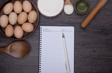 Wooden background with baking ingredients (eggs, flour and rolling pin) over rustic texture. Top view. Space for text. Food or cooking concept.