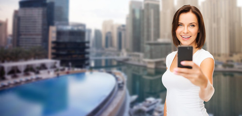 woman taking picture by smartphone over dubai city