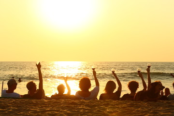 joy/ friends sitting on the beach to see a sunset