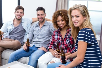 Happy multi-ethnic friends holding beer while sitting on sofa