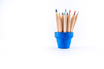 A bunch of pencils in a blue flower pot, isolated on white background.