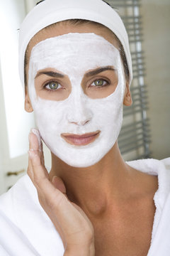 femme se faisant un masque de beauté dans sa salle de bain