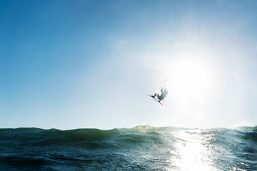Surfer jumping in front of the sun