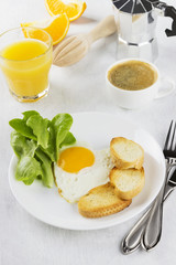 Breakfast: fried eggs with greens, orange juice, coffee on a whi