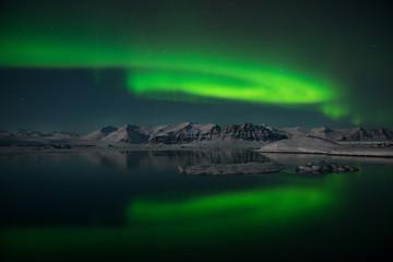 The Northern Lights dance over the glacier lagoon Jokulsarlon, Iceland