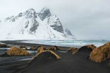 Stokksnes Peninsula, Vestrahorn mountains and black sand dunes over the ocean, winter landscape, Iceland