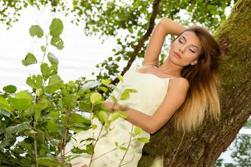 Obraz Rozmarzona kobieta przy drzewie. - fototapety do salonu
