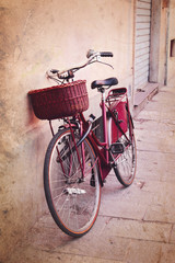 Vintage red bicycle with wicker basket at the street in Italy