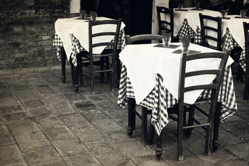 Restaurant tables at the street. Old photo effect applied.