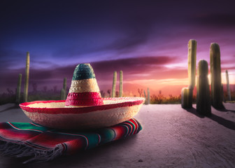 "Mexican hat ""sombrero"" on a ""serape"" in a mexican desert at twil"