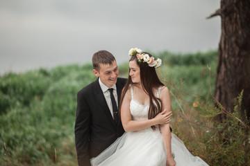 Elegant beautiful wedding couple posing near lake in park