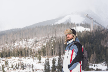 Bearded man wearing hat with ear flaps in cold day, a mountain in background