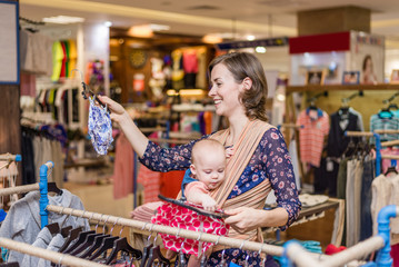 Young woman with baby in a sling in shopping centre