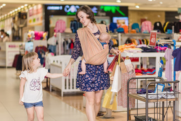 Young mother with two daughters makes purchases in shopping centre