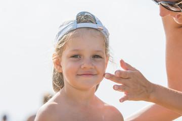 Mom rubs sunscreen face pretty child