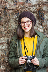 Smiling hipster girl standing in front of the wall and takeing a pictures.