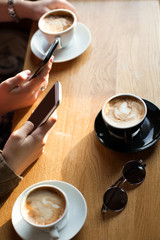 Closeup of hands with coffee cups and smartphones