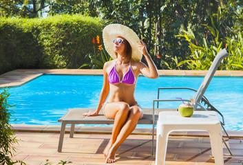 Woman in swimwear,  hat  and sunglasses sitting near  swimming pool.