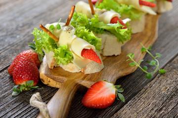 Käseröllchen mit Erdbeeren auf Ciabattabrot mit Salatblatt - Cheese rolls with strawberries on Italian ciabatta bread with lettuce leaves