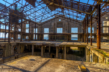 Ruins of an abandoned old factory. The remains of the steel stru