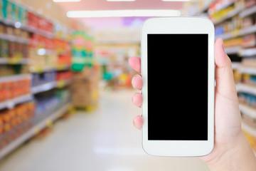 Female hand holding mobile phone on Supermarket blurred backgrou