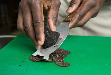 Expensive gourmet Black truffle being sliced thinly on a green cutting board
