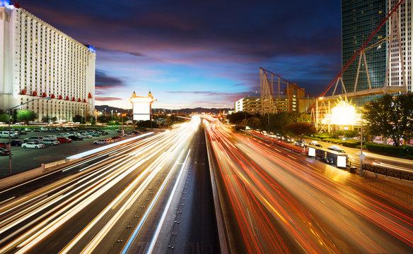 busy traffic on road and modern buildings in purple sky in las vegas