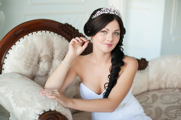 young beautiful bride sits on an elegant sofa and looking at the camera