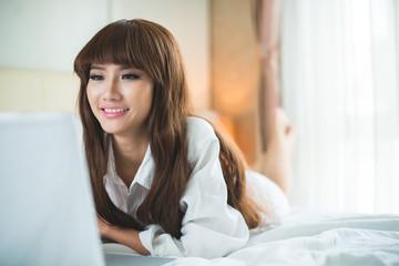 Smiling beautiful Vietnamese girl working on laptop in bed