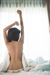 Topless girl stretching in bed, view from the back