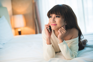 Portrait of smiling beautiful Asian woman on the phone