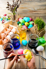 Female hands coloring eggs for Easter holiday