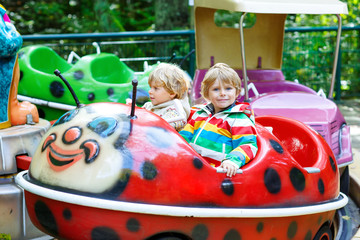 Two little kid boys on carousel in amusement park
