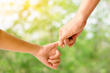 Closeup of mother holding her  children hand on beautiful green nature background.