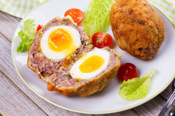 Scotch Eggs Served with Tomato Cherry and Salad on White Plate