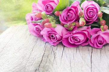 Pink roses on wooden ground, card motive