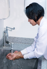 Woman in a laboratory washing her hands in the sink