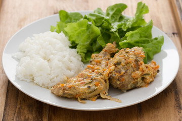 rabbit with sauce,  boiled rice and salad on white plate