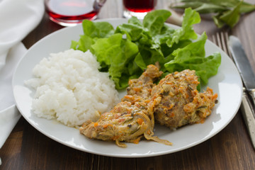 rabbit with boiled rice and lettuce on white plate