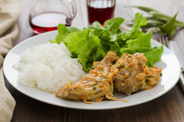 rabbit with sauce,  boiled rice and salad on plate