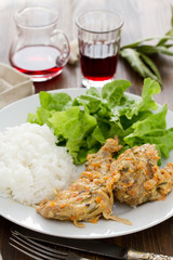 rabbit with boiled rice and salad on white plate on brown wooden background