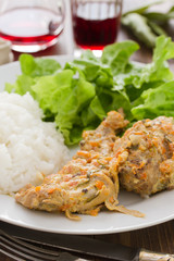 rabbit with sauce,  boiled rice and salad on plate and red wine