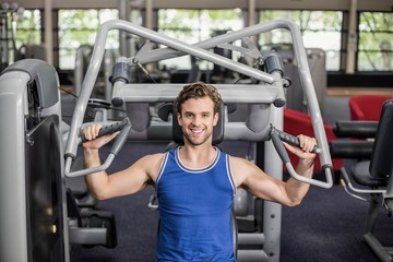 Fit man using weight machine