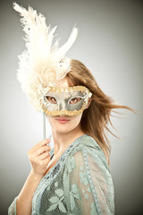 beautiful blonde girl with old carnival mask isolated on grey