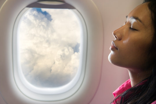 woman sleeping in an airplane at the window